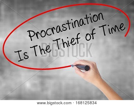 Woman Hand Writing  Procrastination Is The Thief Of Time With Black Marker Over Transparent Board