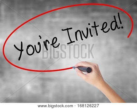 Woman Hand Writing You're Invited! With Black Marker Over Transparent Board