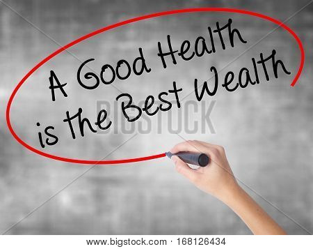 Woman Hand Writing A Good Health Is The Best Wealth With Black Marker Over Transparent Board