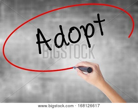 Woman Hand Writing Adopt  With Black Marker Over Transparent Board