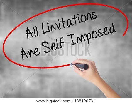 Woman Hand Writing All Limitations Are Self Imposed With Black Marker Over Transparent Board