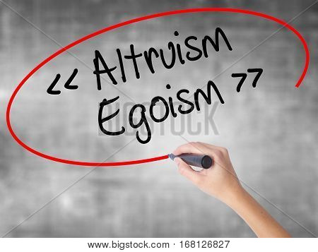 Woman Hand Writing Altruism - Egoism With Black Marker Over Transparent Board.