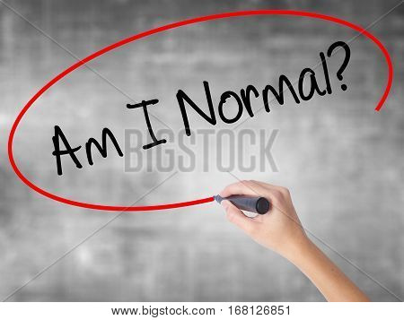 Woman Hand Writing Am I Normal? With Black Marker Over Transparent Board