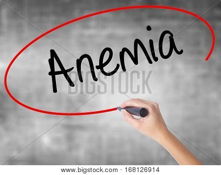 Woman Hand Writing Anemia With Black Marker Over Transparent Board.