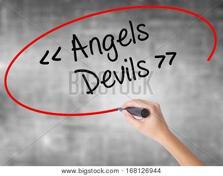 Woman Hand Writing Angels - Devils With Black Marker Over Transparent Board.
