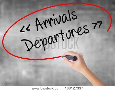 Woman Hand Writing Arrivals - Departures With Black Marker Over Transparent Board.