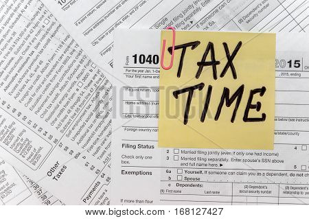 Tax Time written on yellow sticker note with paperclip to tax form