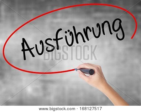 Woman Hand Writing Ausfuhrung (execution In German) With Black Marker Over Transparent Board