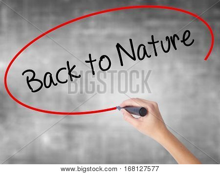 Woman Hand Writing Back To Nature With Black Marker Over Transparent Board