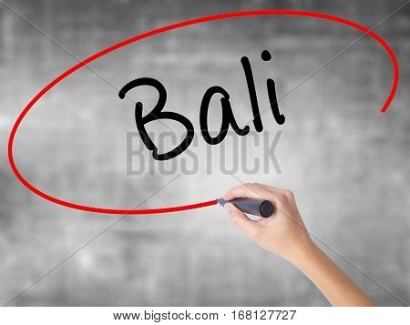 Woman Hand Writing Bali  With Black Marker Over Transparent Board