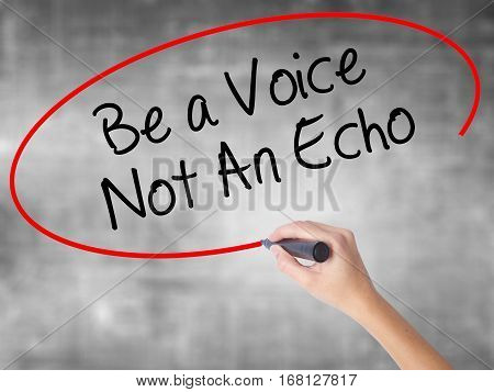 Woman Hand Writing Be A Voice Not An Echo With Black Marker Over Transparent Board