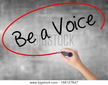 Woman Hand Writing Be A Voice With Black Marker Over Transparent Board