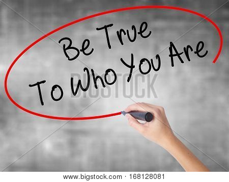Woman Hand Writing Be True To Who You Are With Black Marker Over Transparent Board
