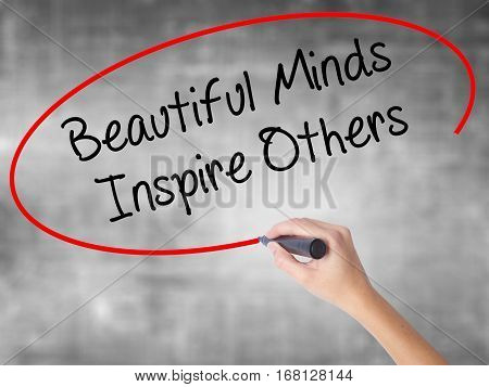 Woman Hand Writing Beautiful Minds Inspire Others With Black Marker Over Transparent Board