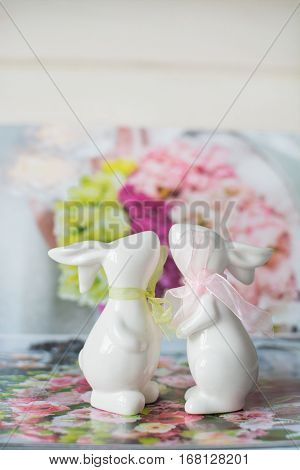 Two cute ceramic rabbits in love on the flower background. St. Valentine's Day. kiss. February 14.