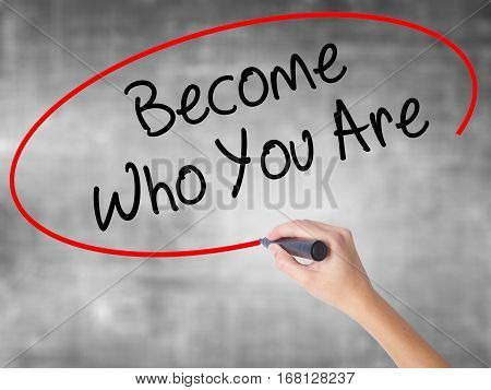 Woman Hand Writing Become Who You Are With Black Marker Over Transparent Board