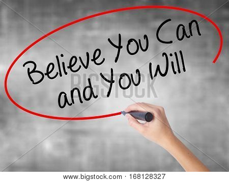 Woman Hand Writing Believe You Can And You Will With Black Marker Over Transparent Board