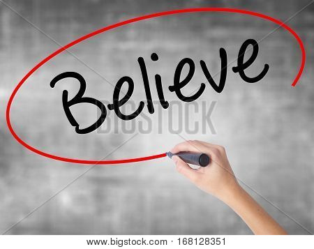 Woman Hand Writing Believe With Black Marker Over Transparent Board