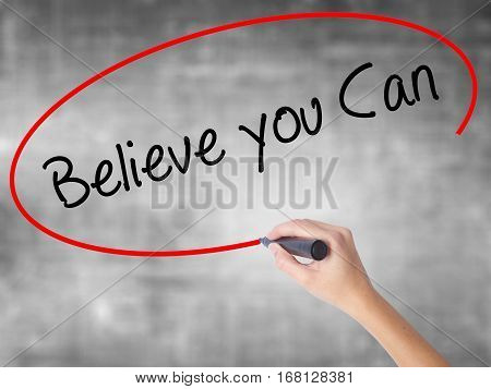 Woman Hand Writing Believe You Can With Black Marker Over Transparent Board