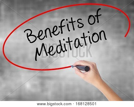 Woman Hand Writing Benefits Of Meditation With Black Marker Over Transparent Board.