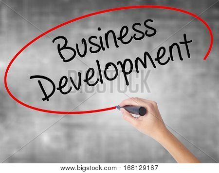 Woman Hand Writing Business Development With Black Marker Over Transparent Board.