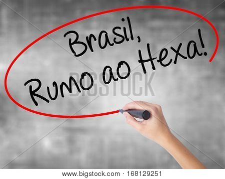 Woman Hand Writing Brasil, Rumo Ao Hexa! With Black Marker Over Transparent Board.