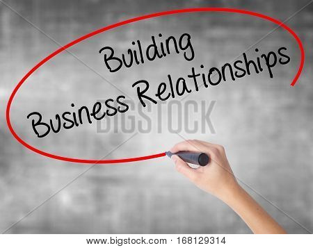 Woman Hand Writing  Building Business Relationships  With Black Marker Over Transparent Board
