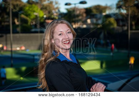 Fair skinned red head woman smiling while wearing black athletic jacket.