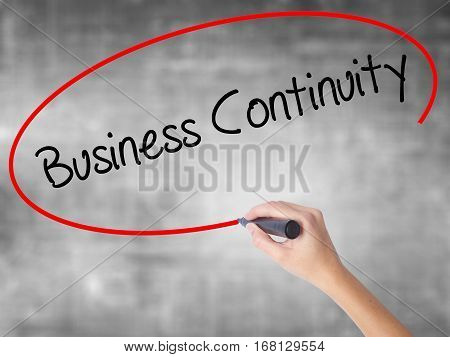 Woman Hand Writing Business Continuity With Black Marker Over Transparent Board