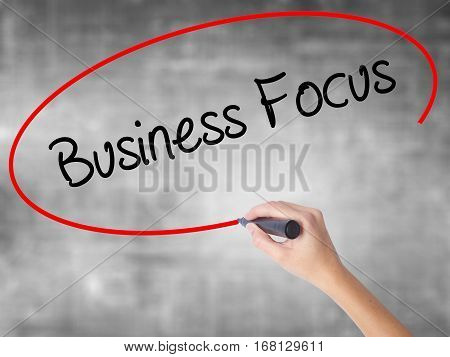 Woman Hand Writing Business Focus With Black Marker Over Transparent Board.