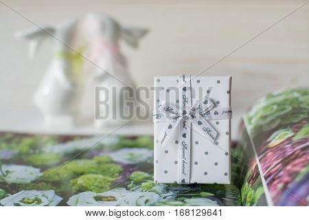 Two cute ceramic rabbits and a gift box on the white flower wooden background. St. Valentine's Day. kiss. February 14.