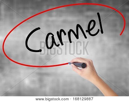 Woman Hand Writing Carmel With Black Marker Over Transparent Board