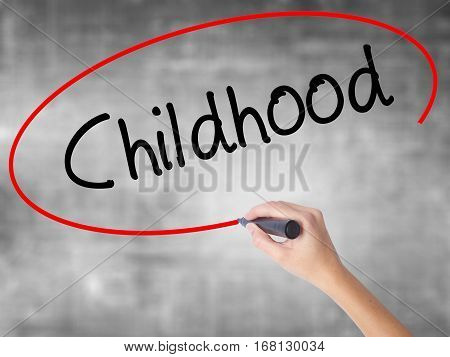 Woman Hand Writing Childhood With Black Marker Over Transparent Board
