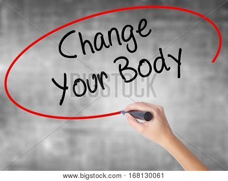 Woman Hand Writing Change Your Body With Black Marker Over Transparent Board.