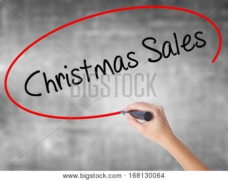 Woman Hand Writing Christmas Sales With Black Marker Over Transparent Board