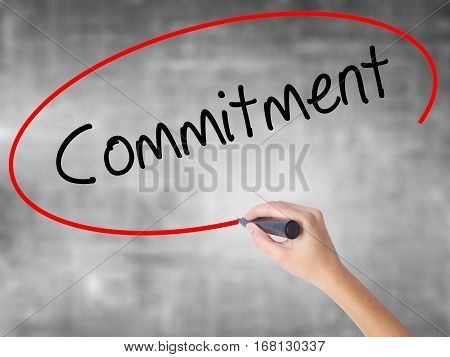Woman Hand Writing Commitment With Black Marker Over Transparent Board.