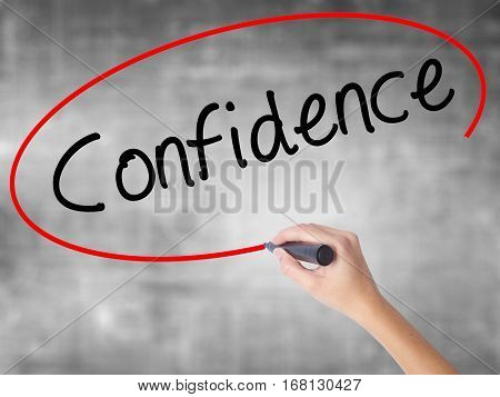 Woman Hand Writing Confidence With Black Marker Over Transparent Board