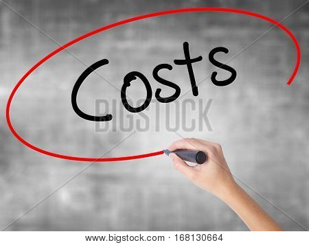 Woman Hand Writing Costs  With Black Marker Over Transparent Board