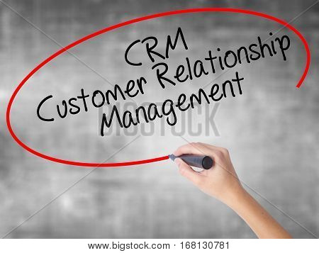 Woman Hand Writing Crm Customer Relationship Management  With Black Marker Over Transparent Board