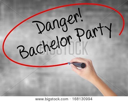 Woman Hand Writing Danger! Bachelor Party With Black Marker Over Transparent Board