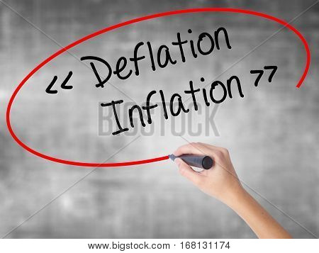 Woman Hand Writing Deflation - Inflation With Black Marker Over Transparent Board.