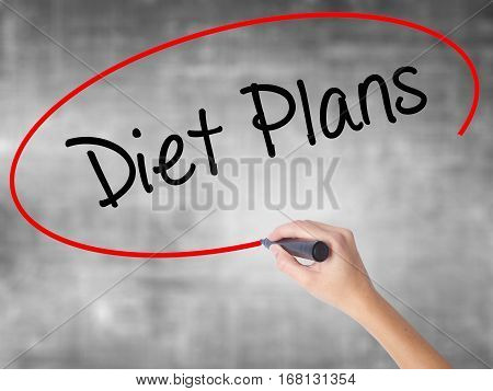 Woman Hand Writing  Diet Plans  With Black Marker Over Transparent Board
