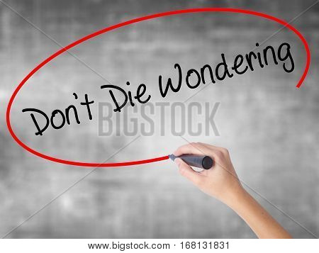 Woman Hand Writing Don't Die Wondering With Black Marker Over Transparent Board
