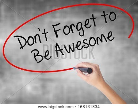 Woman Hand Writing Don't Forget To Be Awesome With Black Marker Over Transparent Board