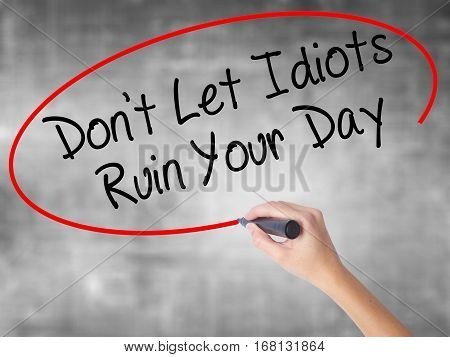 Woman Hand Writing Don't Let Idiots Ruin Your Day With Black Marker Over Transparent Board