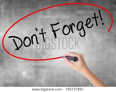 Woman Hand Writing Don't Forget!  With Black Marker Over Transparent Board