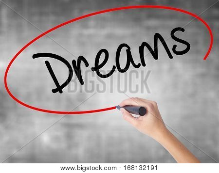 Woman Hand Writing Dreams With Black Marker Over Transparent Board