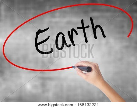Woman Hand Writing Earth With Black Marker Over Transparent Board.