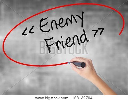 Woman Hand Writing Enemy - Friend With Black Marker Over Transparent Board.