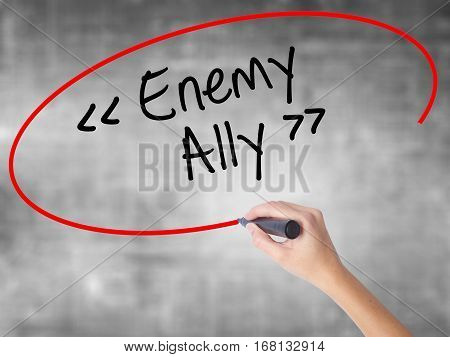 Woman Hand Writing Enemy - Ally With Black Marker Over Transparent Board.